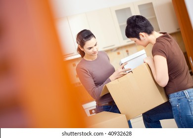 Two young women packing up cardboard boxes in kitchen during moving to new home.