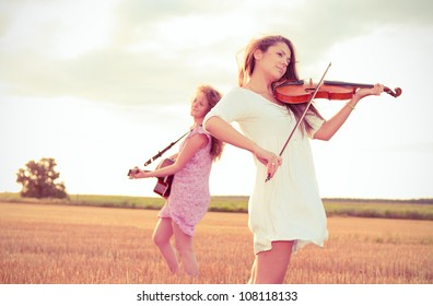 Two young women playing guitar and violin outdoors on the field in summer evening. Split toning.