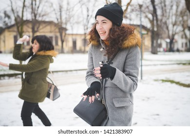 two young women playing in park with snow cover – joyful, cheerful, communication