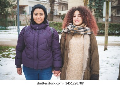 two young women posing for photo and smiling– joyful, multicultural, communication
