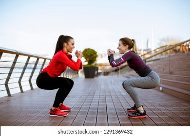 Two young women practice stretching outdoor on rivers promenade
