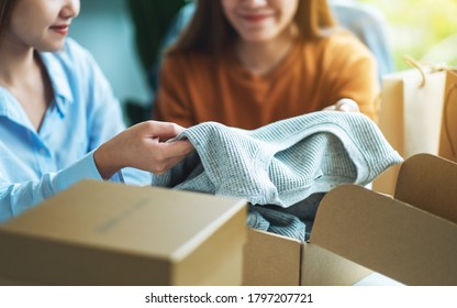 Two young women receiving and opening a postal parcel box of clothing at home for delivery and online shopping concept