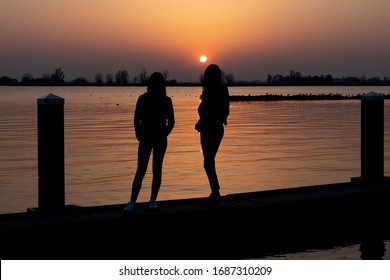Two young women relaxing during  sunset on a landing stage at the Lake Zoetermeerse Plas in Zoetermeer, The Netherlands 1