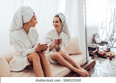 Two young women are relaxing in spa and wellness center. Talking and drinking tea together.