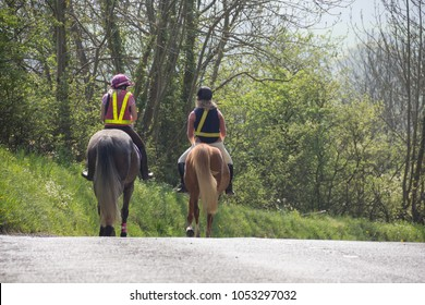 Two young women riding horses along country lanes in rural Shropshire wearing all the correct safety gear to be safe and be seen by other road users.