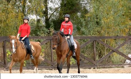 Two young women riding horses. Two girls equestrians in helmets riding horses on training ground, front view. People, leisure, animals, active lifestyle.