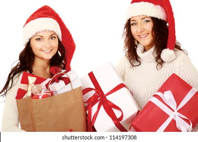 Two young women with Santa hat holding shopping bags, isolated on white background