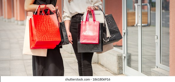 Two young women with shopping bags standing near the shopping mall outdoors