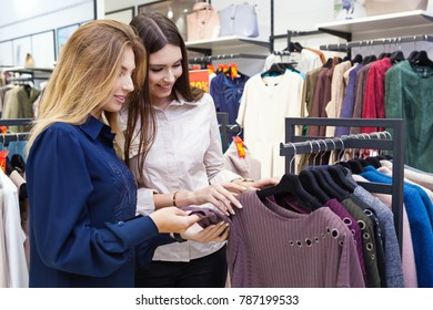 Two young women shopping and looking at some clothing in a store.