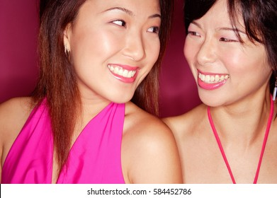 Two young women side by side smiling at each other