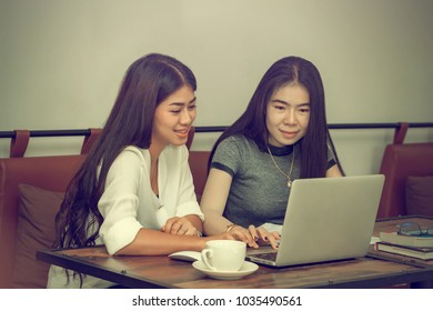 Two young women sit at the desk. Young businesswoman sitting at work desk