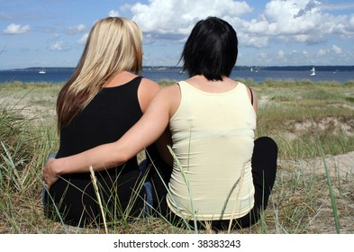 Two young women sitting at the beach holding each other