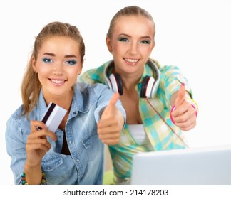 Two young women sitting with laptop  and credit cart showing ok