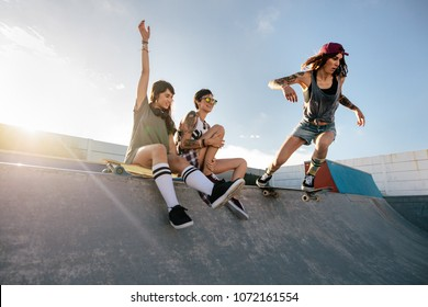 Two young women sitting on skating ramp with a girl practising skateboarding. Skateboarding woman riding skateboard at skate park ramp with friends sitting by.