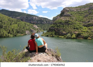 Two young women sitting on a rock and watching the landscape. On the background a lake between green mountains.