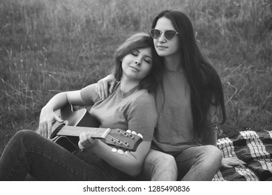 Two young women sitting outdoors and play the guitar. Black and white