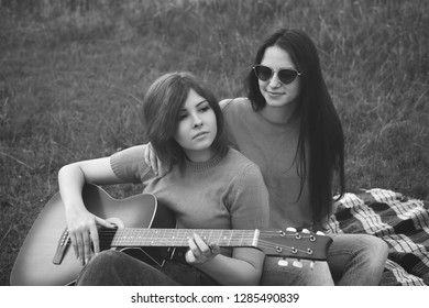Two young women sitting outdoors and play the guitar. Best friends Black and white