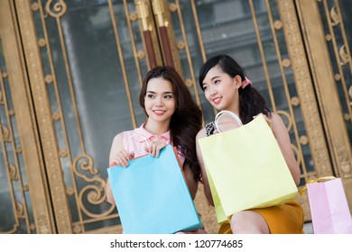 Two young women sitting with purchases at the shop