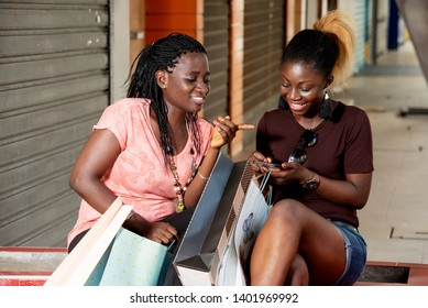 two young women sitting with shopping bags in their hands after shopping. women show what they have in a shopping bag and look on a cell phone.