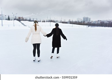 Two young women skating on ice rink rear view