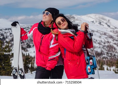 Two young women with ski and snowboard on ski holiday in mountains