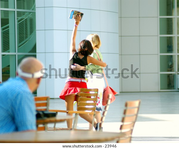 Two young women skipping carefree through a public courtyard