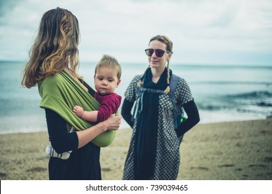 Two young women with a small baby are standing on the beach