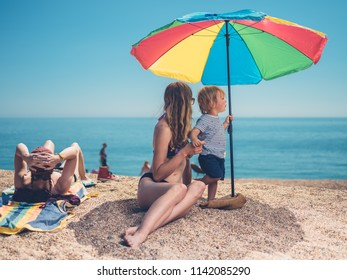 Two young women and a small child are relaxing on the beach in summer