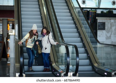 Two young women with small luggage on the escalator at the airport. The girlfriends are in a good mood. Traveling by plane is speed and comfort.