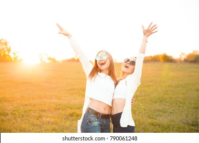 Two young women standing against sunset on the spring grass field