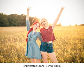 Two young women standing on the background of sunset. Best friends