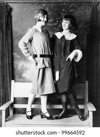 Two young women standing on a bench smiling and looking at each other