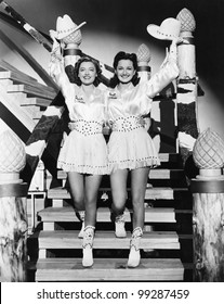 Two young women stepping down a staircase waving their western hats