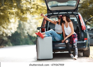 Two young women with suitcases on car trip.They are sitting in car back and resting after long ride.Taking selfie.