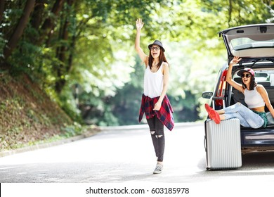 Two young women with suitcases on car trip. Their car broke down and they are trying to get help.