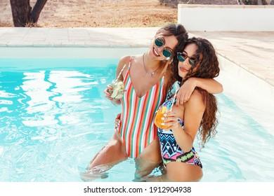 Zwei junge Frauen in Badeanzügen zum Entspannen und trinken tropische Cocktails im Pool Draufsicht Nahaufnahme