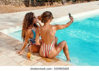 Zwei junge Frauen in Badeanzügen, die sich mit einem Handy selbst machen und tropische Cocktails im Pool trinken