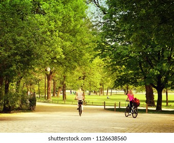 two young women  take a ride with bike at Englischer Garten, green oasis in the middle of Munich