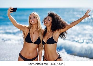 Two young women taking selfie photograph with smart phone in swimwear on a tropical beach. Funny caucasian and arabic females wearing black bikini.