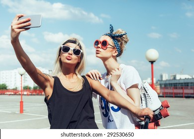 two young women taking selfie with mobile phone. Swag teen girls. Outdoor lifestyle portrait