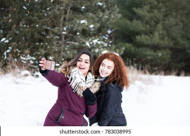 Two young women taking a selfie outdoors in the winter.