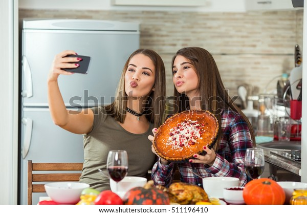 Two young women are taking selfies with their smart phone. They are taking pictures of food they made for Thanksgiving dinner.