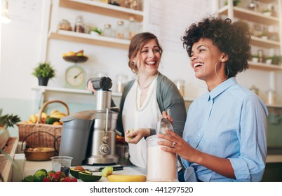 Two young women talking and smiling while working at bar counter. They are preparing fruit juice.