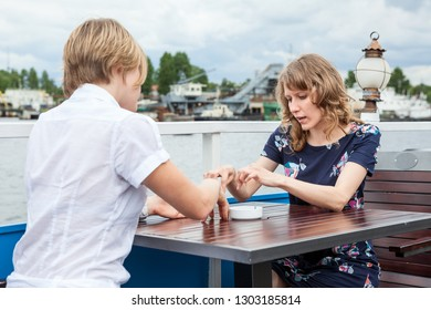 Two young women talking together while sitting at the table in summer cafe, voyage on the river