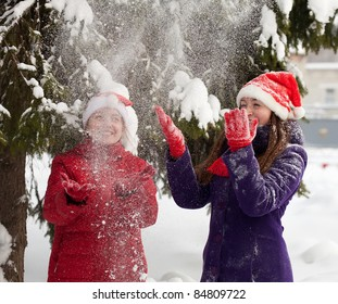 Two  young women throwing snow  in the air in park