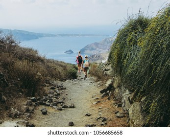 Two young women, tourists hike on the edge of the caldera by the the Aegean Sea. Fira to Oia( on background) in Santorini Greece in autumn.