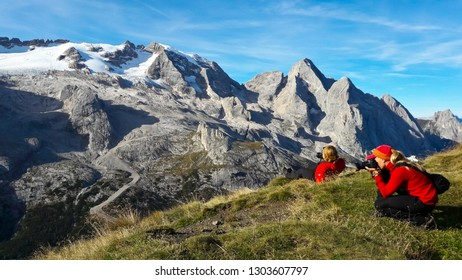 Two young women tourists taking picture of mountain landscape.  Marmolada Glacier. Dolomiti, Itay. Alps.
