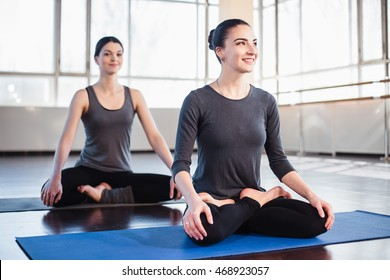 Two young women in a traditional yoga pose