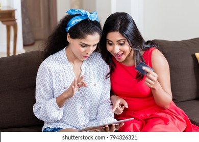 Two young women using a tablet PC for online payment with the credit card