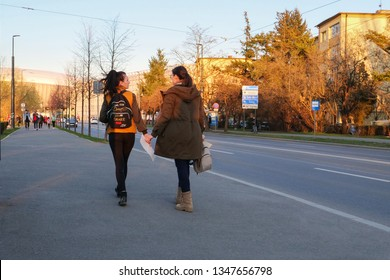 Two young women walk on the sidewalk in the evening in Cluj-Napoca, Romania, March 23, 2019